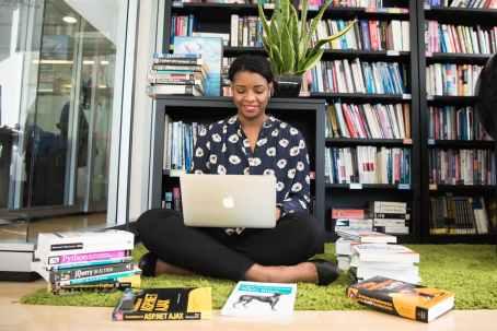 woman in black shirt using macbook